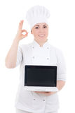 Cook woman holding laptop with empty screen and showing ok sign Stock Photography
