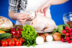 Cook woman holds a Crude Hen Royalty Free Stock Photography