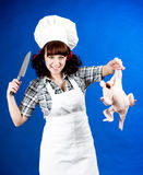 Cook woman holds a Crude hen and knife Royalty Free Stock Photography