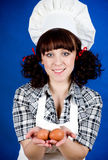 Cook woman holds a easter eggs Stock Photography