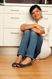 Cook woman sitting on the kitchen floor Stock Photo
