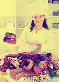 Cook woman with smoked products Royalty Free Stock Photography