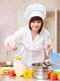 Cook woman in toque cooks in kitchen Stock Photography