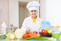 Cook woman  in uniform cutting vegetables Royalty Free Stock Photos