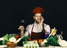 Cook works in kitchen near vegetables and tools. Italian drink and sommelier concept. Man in hat and apron. Shows Perfect Taste sign. Chef with satisfied face stock photos