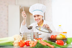 Cook works with ladle at  kitchen Royalty Free Stock Image