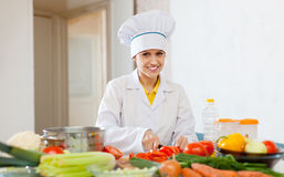 Cook works with vegetables at commercial kitchen Stock Photos