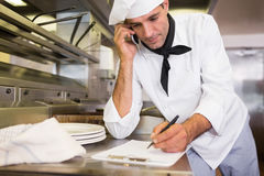 Cook writing on clipboard while using cellphone in kitchen Stock Photos