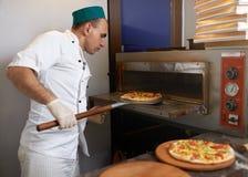 Cook wziąć pizzę od piekarnika przygotowywającego Fotografia Royalty Free