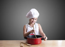 Cook. Young girl in the kitchen with chef clothing Royalty Free Stock Image