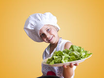 Cook. Young girl in the kitchen with chef clothing Royalty Free Stock Images