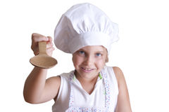Cook. Young girl in the kitchen with chef clothing Royalty Free Stock Photography