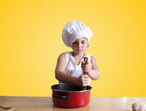 Cook. Young girl in the kitchen with chef clothing Royalty Free Stock Photos