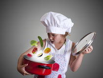 Cook. Young girl in the kitchen with chef clothing Stock Image