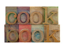 Cookbook. The word cookbook in vintage wooden letterpress type blocks, stained by color ink, isolated on white Stock Image