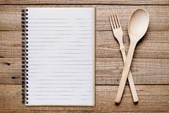 Cookbook, fork and spoon on wooden table Royalty Free Stock Image