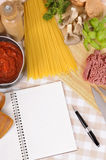 Italian pasta cookbook with ingredients for spaghetti bolognese, copy space, vertical. Making Italian spaghetti bolognese with ingredients and blank recipe book Stock Photos