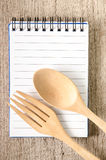 Cookbook and kitchenware on wooden background Stock Photography