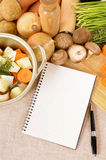 Cookbook or notepad with casserole dish and organic vegetables on kitchen worktop, copy space, vertical Royalty Free Stock Images