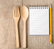 Cookbook,pencil and kitchenware on wooden background Royalty Free Stock Images