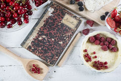 Cookbook with red fruits. On the wooden table royalty free stock images
