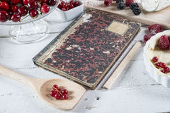Cookbook with red fruits. On the wooden table stock images