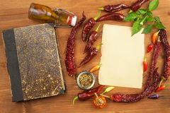 Cookbook and spices on wooden table. Cookbook and ingredients. Garlic, chili peppers and onion. Ingredients for cooking. Stock Photography
