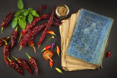 Cookbook and spices on wooden table. Cookbook and ingredients. Garlic, chili peppers and onion. Ingredients for cooking. Stock Images