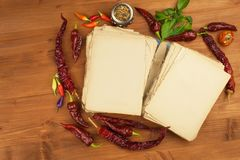 Cookbook and spices on wooden table. Cookbook and ingredients. Garlic, chili peppers and onion. Ingredients for cooking. Royalty Free Stock Photo