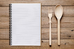 Cookbook, spoon and fork on wooden table Royalty Free Stock Photo