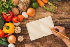 cookbook Verduras frescas alrededor del cuaderno abierto en backgr rústico imagen de archivo