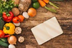 cookbook Verduras frescas alrededor del cuaderno abierto en backgr rústico imagen de archivo libre de regalías