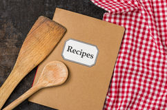 Cookbook with wooden spoons on a red checkered tablecloth Royalty Free Stock Photography