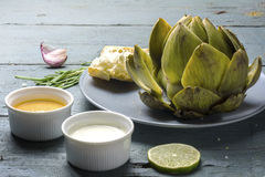 Cooked artichoke with dips and bread on rustic gray blue wood Royalty Free Stock Photo