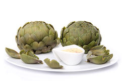 Cooked artichoke with a vinaigrette sauce on a plate Royalty Free Stock Image