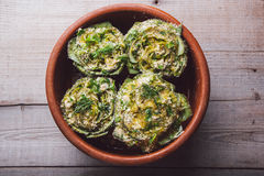 Cooked artichokes with parsley and parmesan, served in a clay dish on a wooden table Stock Image