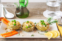 Cooked Artichokes with rice, green peas, carrot and olive oil. Stock Photos