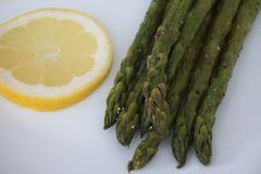 Cooked asparagus and slice of lemon Royalty Free Stock Photos