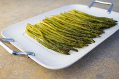 Cooked asparagus on a white plate. Cooked asparagus on a white square plate on concrete countertop Stock Image