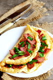Cooked bacon omelet. Homemade spicy omelet with fried sliced bacon and parsley on a white plate, fork, knife on old wooden table Stock Images