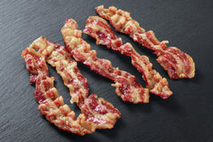 Cooked bacon rashers. On the background of a slate board Stock Photos