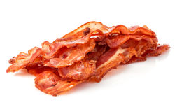 Cooked bacon rashers close-up on a white background royalty free stock image