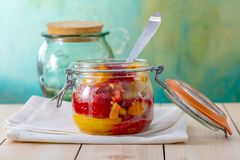 Cooked baked red yellow sweet peppers in a glass jar and fork on a wooden table. royalty free stock images