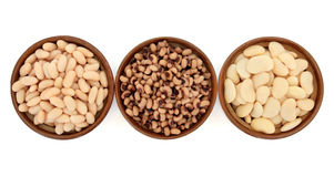 Cooked Beans and Peas. Cooked bean and pea varieties of cannelini, black eyed peas and butter beans in terracotta bowls over white background stock photography