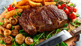 Cooked Beef Ribeye Steak with Potato, Mushrooms, tomatoes on wooden board. Stock Photo