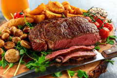 Cooked Beef Ribeye Steak with Potato, Mushrooms, tomatoes on wooden board. Stock Photography