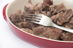 Cooked beef served in a red bowl with fork Royalty Free Stock Photos