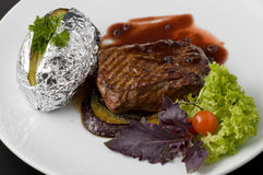 Cooked beefsteak. On white plate royalty free stock image
