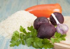 Cooked beets. Bell pepper, garlic and rice on the table and cutting board Royalty Free Stock Photography
