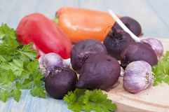 Cooked beets, bell pepper, garlic. On the table and cutting board Royalty Free Stock Images